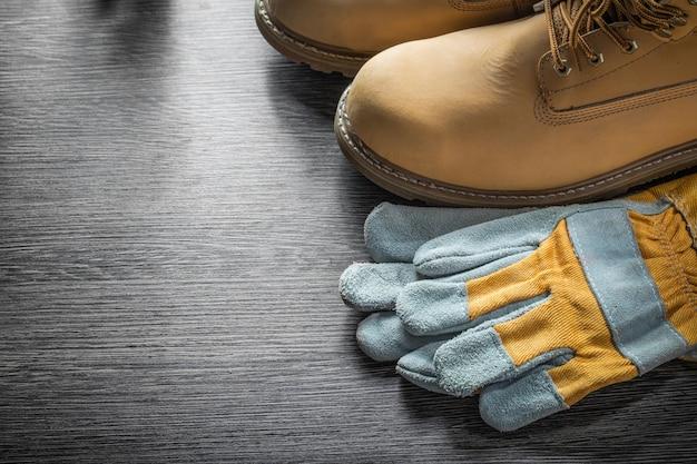 Arbeitsschuhe für schutzhandschuhe auf holzbrett