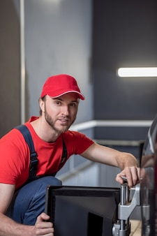 Arbeitsstimmung. erfahrene junge bärtige auto-servicemitarbeiter in overalls und kappe mit achsvermessung stehen in der nähe des autos