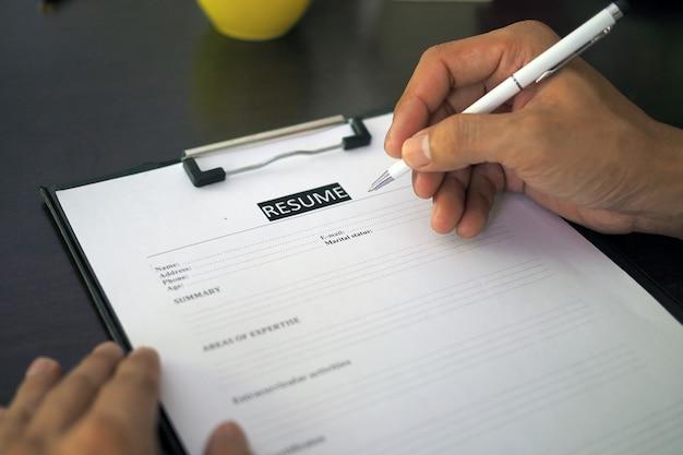 Arbeitssuchende, männer füllen einen lebenslauf auf dem formular aus.