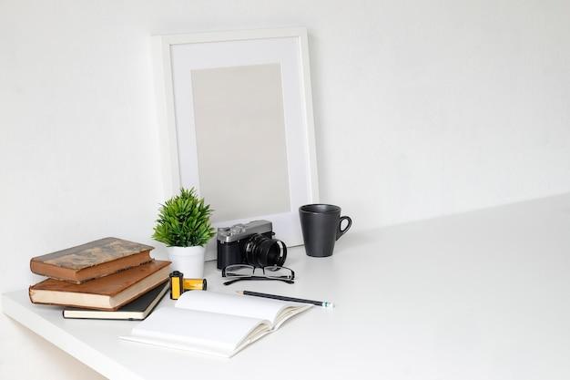 Arbeitstabelle mit fotografiekamera, buch, notizblock und bleistift auf tabelle und leerem fotorahmen.