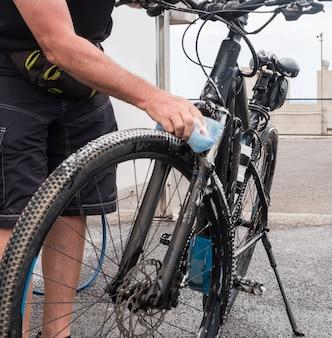 Arbeitstätigkeit. ein senior mit dunkler sportkleidung wäscht sein fahrrad an der tankstelle. draussen. hochdruckpumpe