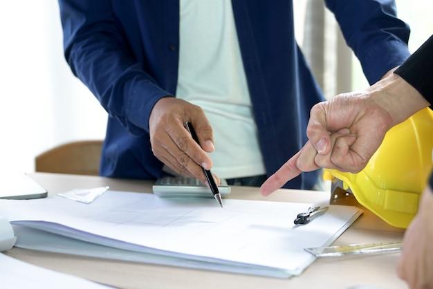 Arbeitstafelarchitekt mit dem zeichnen des grundrissgebäudes und stationär im innenministerium