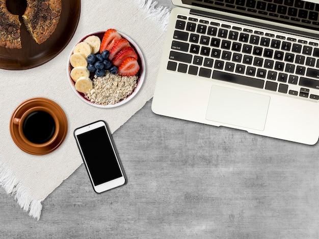 Arbeitstag. computer, handy, kaffee, kuchen und eine gefrorene eis glatte schüssel mit früchten. über einem grauen holzschreibtisch. draufsicht. speicherplatz kopieren.