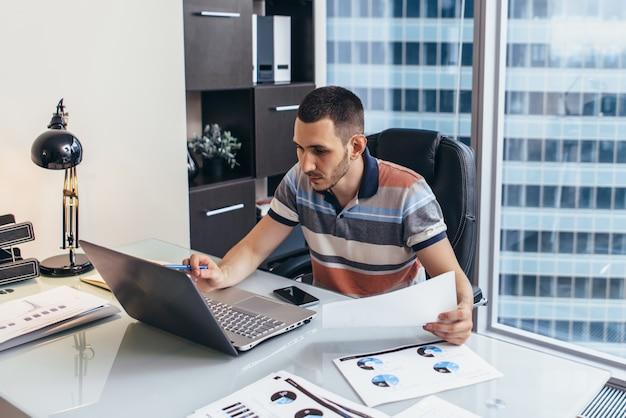 Arbeitstag des finanzanalysten, der auf computeranalyse arbeitet, die mit statistiken arbeitet, die am arbeitsplatz gegen fenster mit stadtbildansicht sitzen.