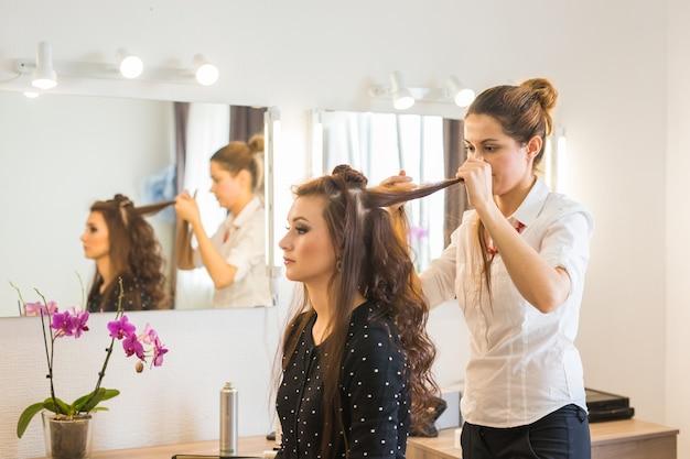 Arbeitstag im schönheitssalon. friseur macht haarstyling.