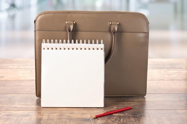 Arbeitstagplanung. modell des leeren leeren notizblocks und der geschäftsmappe, die auf dem tisch stehen