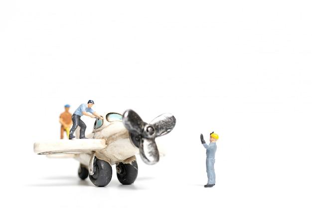 Arbeitsteam, das spielzeugflugzeug auf weißem hintergrund repariert