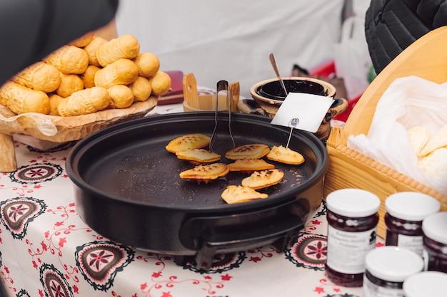 Arbeitstheke, wo gebratener käse zubereitet wird und gläser mit verschiedenen marmeladen stehen. nationale küche. ruhen und reisen. geschmack und genuss. natürliches essen. rezepte und traditionen.
