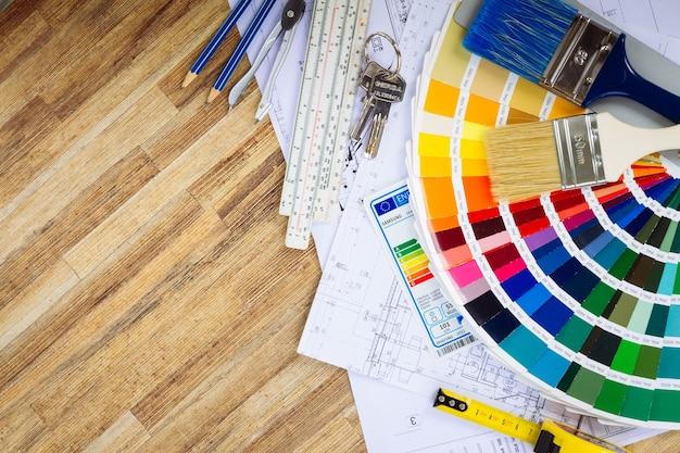 Arbeitstisch des innenarchitekten mit architektonischem grundriss des hauses, farbpalette und pinseln