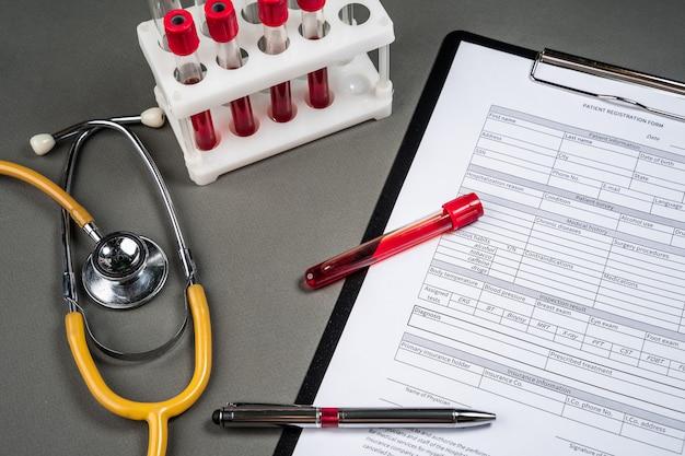 Arbeitstisch des medizinarztes. patientenprofil und stethoskop auf dem tisch. patientenprofil und stethoskop auf dem tisch. der arzt zeichnet die ergebnisse der blutuntersuchung des patienten auf