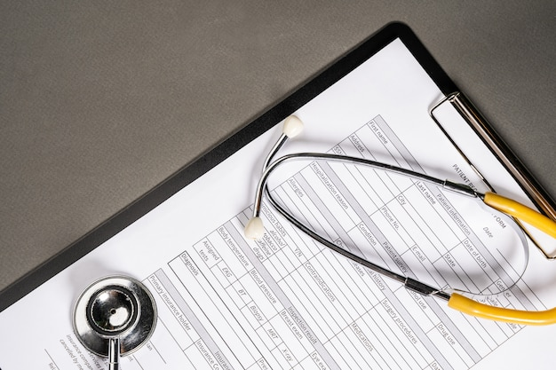 Arbeitstisch des medizinarztes. patientenprofil und stethoskop auf dem tisch.