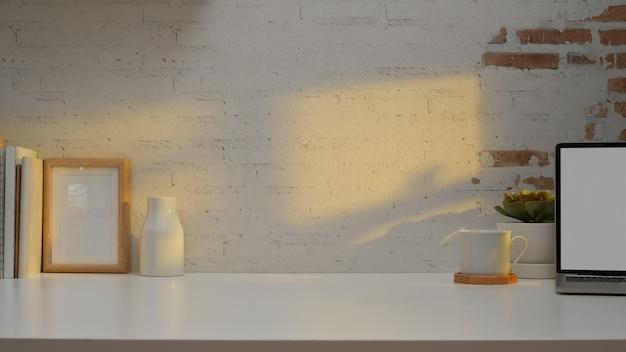 Arbeitstisch im arbeitszimmer mit kopierraum, büchern, dekoration und laptop