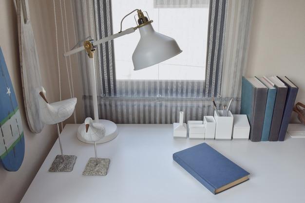Arbeitstisch mit lampe, stiften und büchern im arbeitsraum