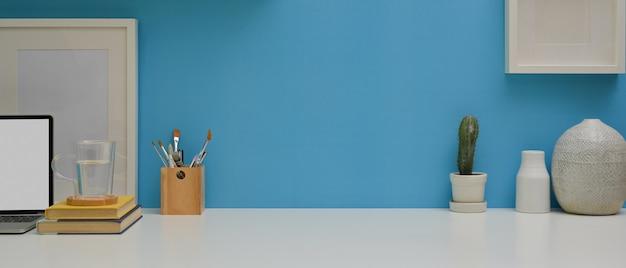 Arbeitstisch mit laptop, schreibwaren, dekorationen und kopierraum im arbeitszimmer