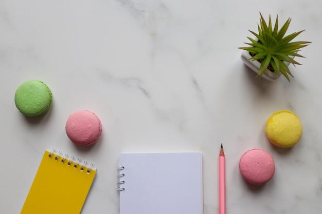Arbeitstisch mit notizblöcken, bleistift, pflanze und makronen auf marmorhintergrund mit kopierraum