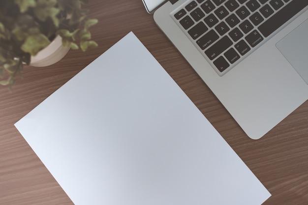 Arbeitstisch mit papier und laptop auf dem holztisch