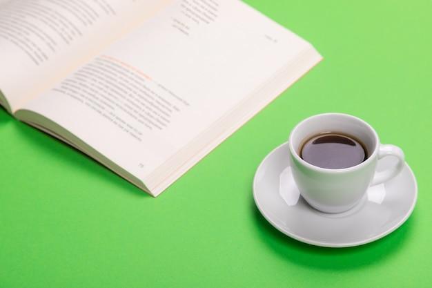 Arbeitstisch mit tasse kaffee und buch lokalisiert auf grünem t-shirt