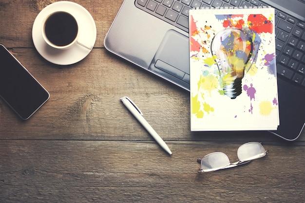 Arbeitstisch mit tastatur, notizblock, telefon, tasse kaffee, gläser und stift auf holztisch