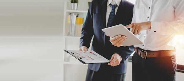 Arbeitstraining. neuer managerchef, der unterrichtende on-line-arbeit mit beweglicher tablette zum jungen praktikantenlehrling steht, der statistikdiagramm lernt und arbeitet im büro