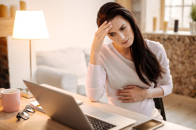 Arbeitsüberbelastung. besorgte nachdenkliche schwangere geschäftsfrau, die stirn berührt, während sie auf bildschirm schaut und auf stuhl sitzt