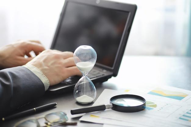Arbeitszeit symbolisiert eine sanduhr. schreibtisch mit versicherungsmanager und bankier. büroangestellter am tisch. das konzept des zeitmangels.