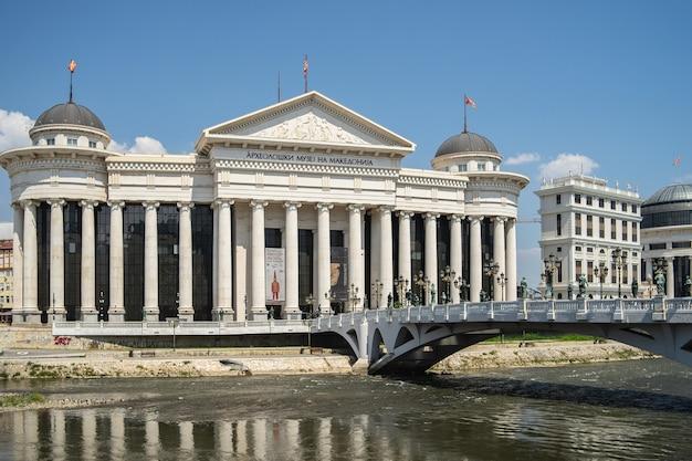 Archäologisches museum von mazedonien, umgeben von einem fluss mit einer brücke darauf in nordmakedonien