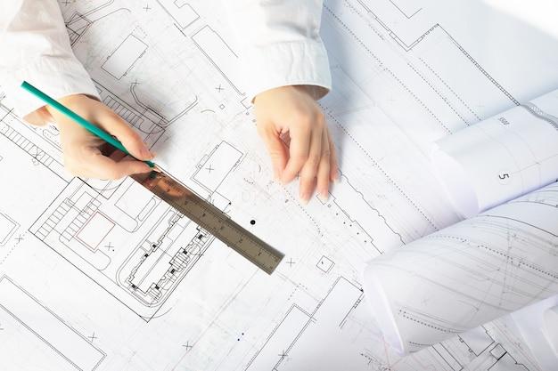 Architekt arbeitet an blaupause. architektenarbeitsplatz - blaupausen, lineal. engineering-tools.