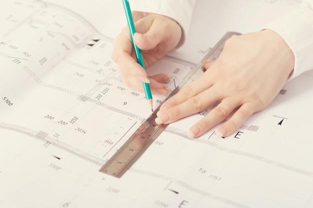 Architekt arbeitet an blaupause, mit architekturprojekt auf der baustelle am schreibtisch im büro