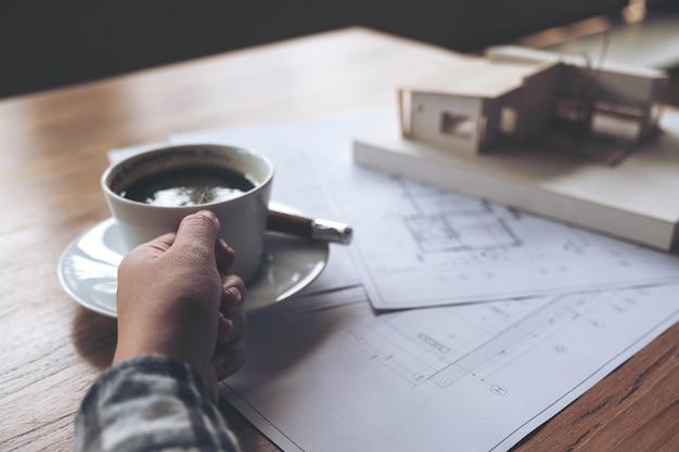 Architekt, der an einem architekturmodell mit geschäftszeichenpapier beim trinken des kaffees arbeitet