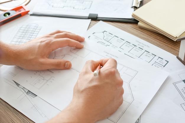Architekt, der an einem projekt des gebäudes im büro arbeitet, nahaufnahme