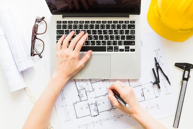 Architekt, der an hausprojekt mit laptop arbeitet