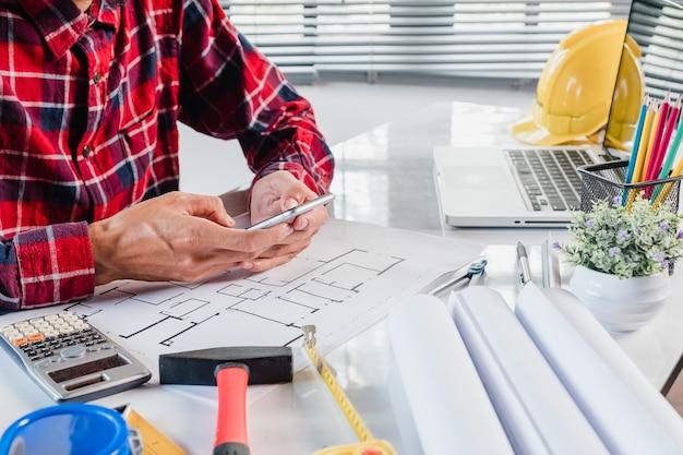 Architekt, der an plan mit plänen, machthaber, taschenrechner, laptop und teilerkompass arbeitet