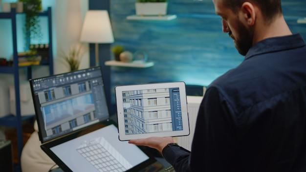 Architekt, der digitales tablet mit gebäudemodell hält