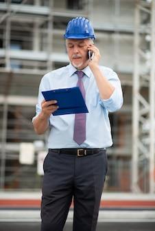 Architekt, der draußen am telefon vor einer baustelle spricht
