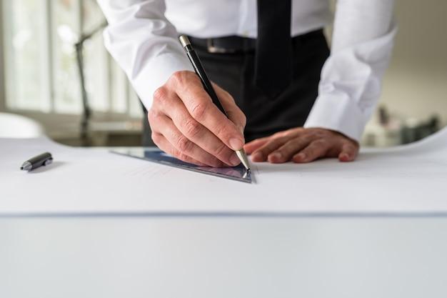 Architekt, der einen entwurf auf einem papier unter verwendung eines bleistifts und eines lineals zeichnet.