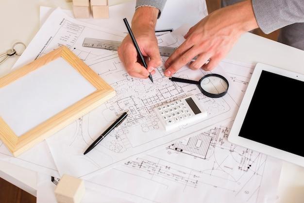 Architekt, der einen plan auf papiermodell zeichnet