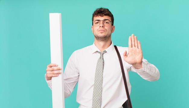 Architekt, der ernst, streng, unzufrieden und wütend aussieht und eine offene handfläche zeigt, die eine stopp-geste macht