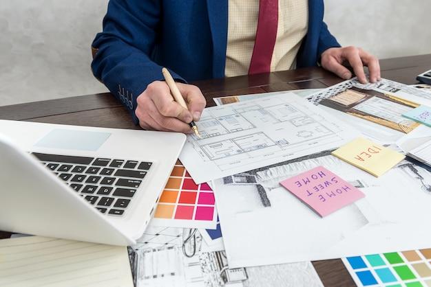 Architekt, der farben für die gebäudedekoration des rauminnenraums mit laptop und farbmuster wählt. innenarchitekt arbeitet mit farbpalette und hausskizze
