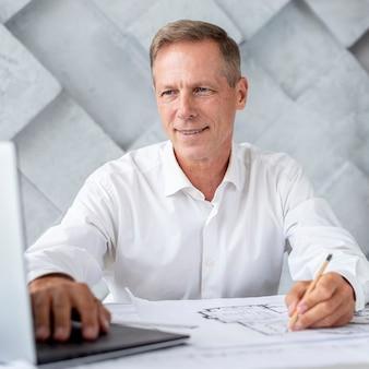 Architekt, der laptop auf ideen überprüft