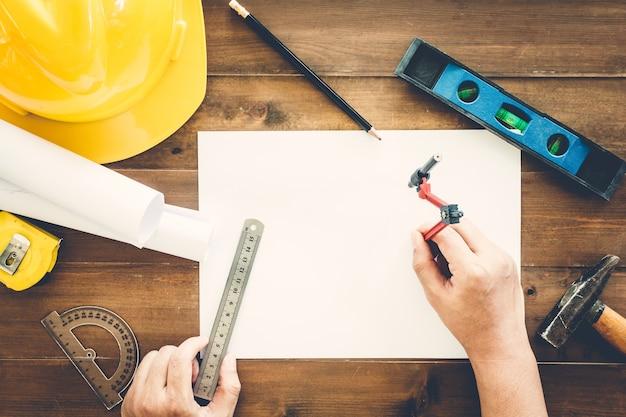 Architekt, der mit bauwerkzeug- und sturzhelmsicherheit auf hölzernem hintergrund arbeitet