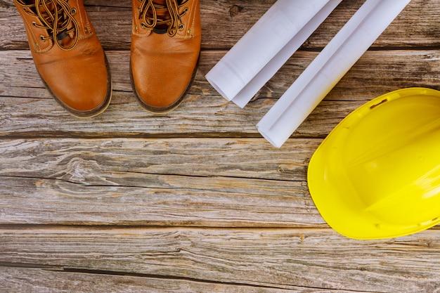 Architekt, der mit blaupausen in der büroansicht arbeitet, die arbeitsstiefel der schützenden arbeitskleidung auf gelbem schutzhelm setzen