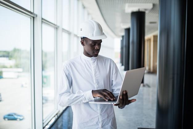 Architekt, der mit computer und bauplänen im büro arbeitet