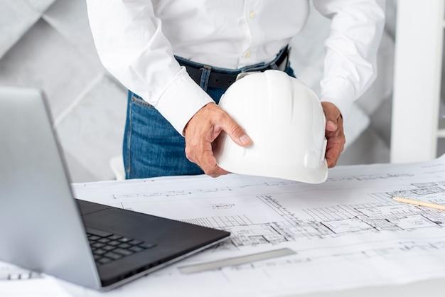 Architekt, der seinen schreibtisch mit werkzeugen vereinbart