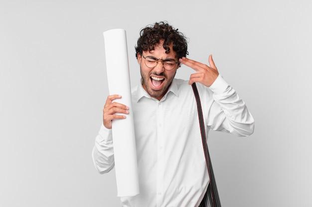 Architekt, der unglücklich und gestresst aussieht, selbstmordgeste, die waffenzeichen mit der hand macht und auf den kopf zeigt