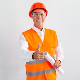 Architekt in der sicherheitsausrüstung, die das gleiche zeichen gibt