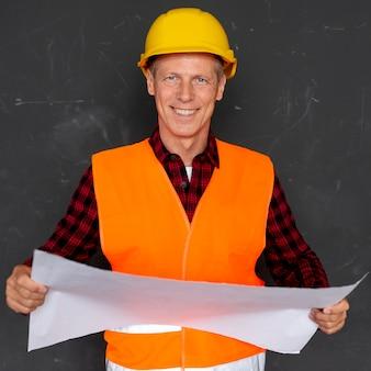 Architekt in der sicherheitsausrüstung mit plänen