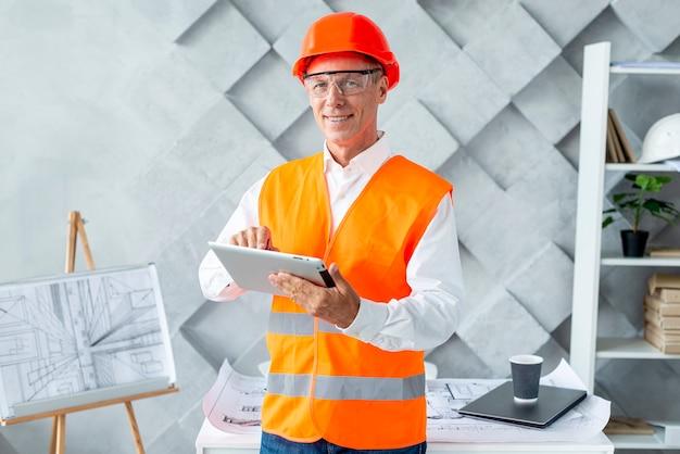 Architekt in der sicherheitsausrüstung unter verwendung der tablette