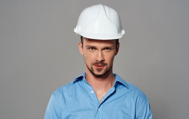 Architekt in einem weißen helm und in einem blauen hemd auf einem grauen wandgefühlsporträt.