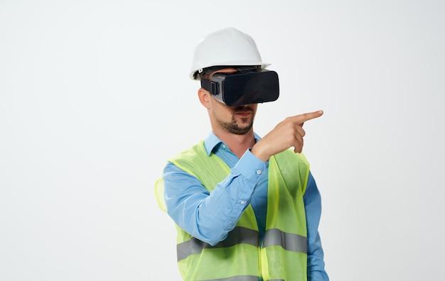 Architekt in einer warnweste und einer 3d-virtual-reality-brille mit weißem helm.
