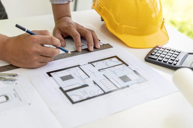 Architekt ingenieur schreibt mit bleistift auf die von ihm entworfenen blaupausen, er überprüft und überarbeitet die zeichnungen, bevor er die arbeit an den kunden schickt. design- und einrichtungsideen.